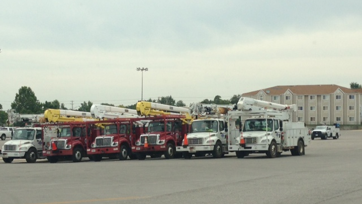 Outfitted vehicles are parked while crew members review safety and restoration procedures before heading out.